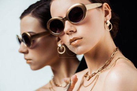 Photo pour Jeune femme nue en lunettes de soleil, bijoux dorés tenant miroir isolé sur noir - image libre de droit