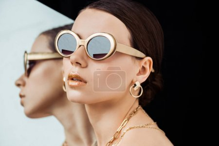 Photo for Young naked woman in sunglasses, golden jewelry near mirror isolated on black - Royalty Free Image