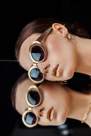 Photo pour Jeune femme en lunettes de soleil, bijou doré couché sur un miroir isolé sur le noir - image libre de droit