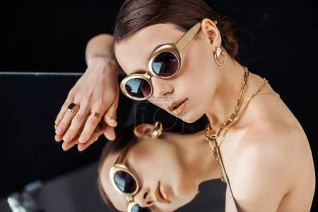 Photo for Young naked woman in sunglasses, golden jewelry lying on mirror isolated on black - Royalty Free Image