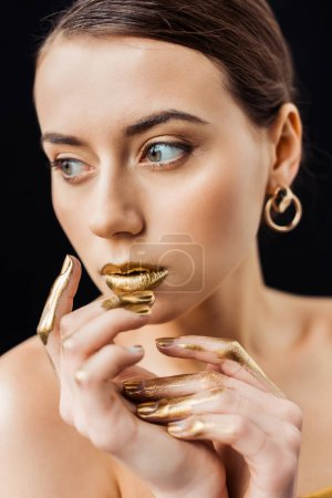 Foto de Young naked woman with golden makeup and golden paint on fingers isolated on black - Imagen libre de derechos