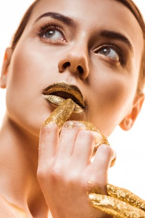 Photo for Young beautiful woman with golden makeup and sparkles on fingers touching lips and looking away isolated on white - Royalty Free Image