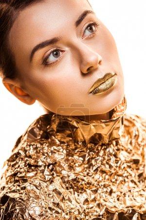Foto de Young beautiful woman with golden lips in golden foil looking away isolated on white - Imagen libre de derechos