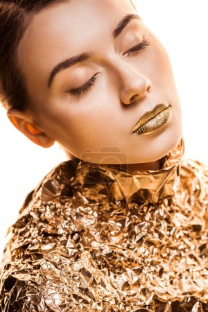 young beautiful woman with closed eyes and golden lips in golden foil isolated on white
