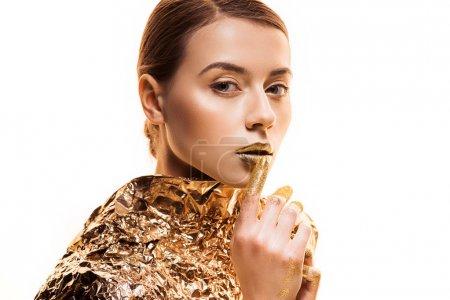 Foto de Young beautiful woman in golden foil touching golden lips isolated on white - Imagen libre de derechos