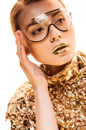 Foto de Young woman with golden lips in golden foil and sunglasses looking away isolated on white - Imagen libre de derechos