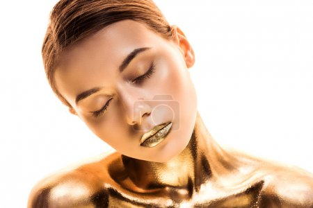young naked woman with closed eyes painted in golden isolated on white