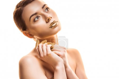 Photo pour Young naked woman with golden lips and fingers looking away isolated on white - image libre de droit