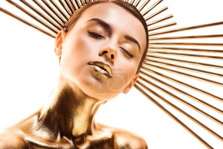 Foto de Desnuda hermosa joven pintada de oro con accesorio en la cabeza y los ojos cerrados aislados en blanco - Imagen libre de derechos