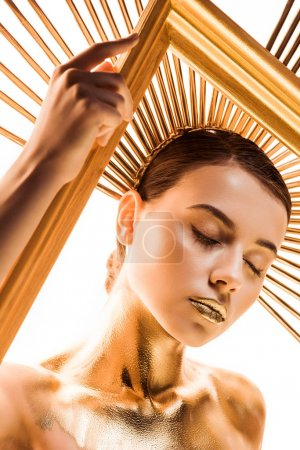 Photo for Nude young woman painted in golden with accessory on head and closed eyes holding frame isolated on white - Royalty Free Image