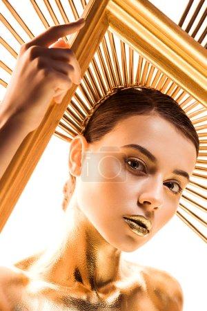 Foto de Hermosa joven pintada de oro con accesorio en la cabeza mirando la cámara y sosteniendo marco aislado en blanco - Imagen libre de derechos
