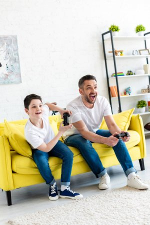 Photo for Excited father and son playing Video Game on couch in Living Room - Royalty Free Image