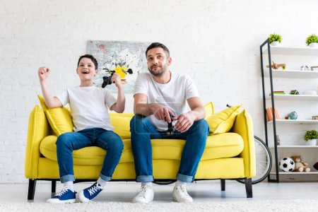 Photo for Excited son cheering while playing Video Game with father on couch at home - Royalty Free Image