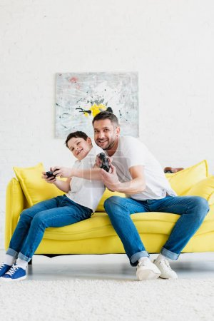 Photo for Happy father and son playing Video Game on couch in Living Room - Royalty Free Image