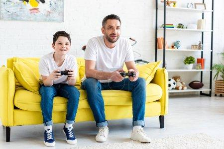 Photo pour Père et fils jouant au jeu vidéo sur le divan dans la salle de séjour - image libre de droit