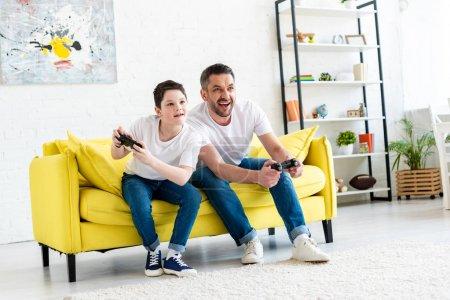 Photo pour Père et fils avec des joysticks jouant au jeu vidéo sur le divan dans la salle de séjour - image libre de droit