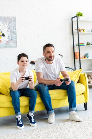 Photo for Father and son with joysticks playing Video Game on couch in Living Room - Royalty Free Image