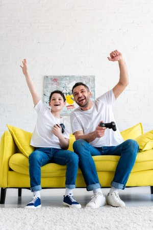 Photo for Father and son cheering while playing Video Game on couch at home - Royalty Free Image