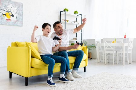Photo for Excited father and son cheering while playing Video Game on couch at home - Royalty Free Image