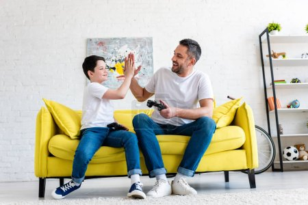 Photo for Father and son doing high five gesture while playing Video Game on couch at home - Royalty Free Image