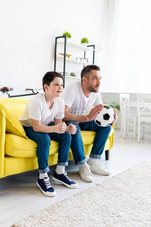 Foto de Father and son watching sports match on couch at home - Imagen libre de derechos