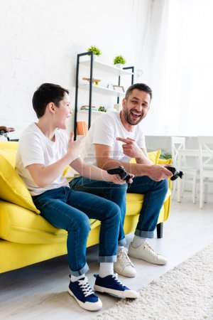 Photo for Excited father and son playing Video Game on couch and pointing with fingers in Living Room - Royalty Free Image