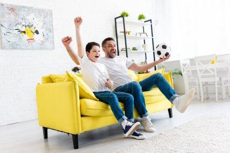 Foto de Padre e hijo emocionados animando y viendo partidos deportivos en el sofá en la sala de estar - Imagen libre de derechos