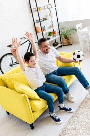 Foto de Padre e hijo emocionados en el sofá viendo partidos deportivos y animando en la sala de estar - Imagen libre de derechos
