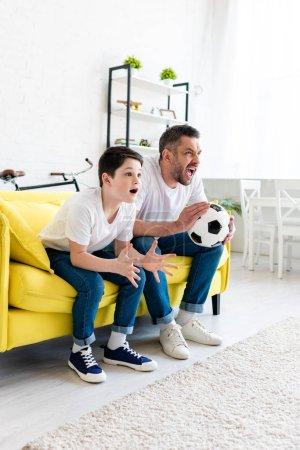 Foto de Padre e hijo emocionados viendo partidos deportivos en el sofá en casa - Imagen libre de derechos