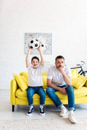Foto de Hijo emocionado con la pelota de fútbol viendo partido de deportes con el padre en la sala de estar - Imagen libre de derechos
