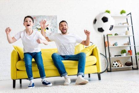 Foto de Padre e hijo emocionados animando mientras ve el partido de deportes en la sala de estar - Imagen libre de derechos