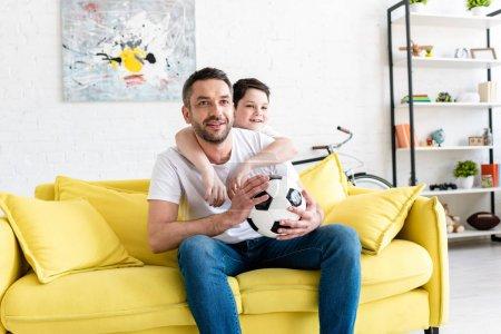 Foto de Padre e hijo viendo partido deportivo en el sofá con la pelota de fútbol en casa - Imagen libre de derechos