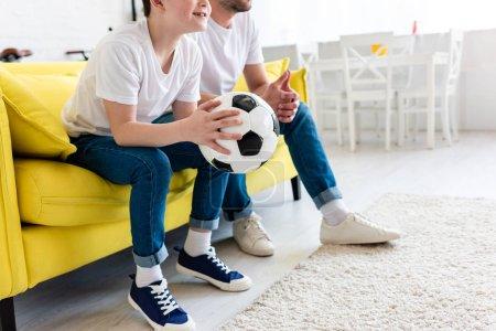 Foto de Vista recortada de padre e hijo viendo partido deportivo en el sofá con pelota de fútbol en casa - Imagen libre de derechos