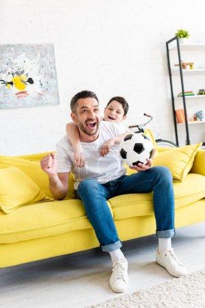 Foto de Padre e hijo emocionados viendo partidos deportivos y animando en la sala de estar - Imagen libre de derechos