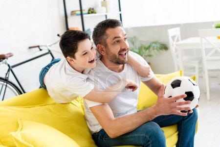 Foto de Padre feliz e hijo viendo partido deportivo en el sofá con la pelota de fútbol en casa - Imagen libre de derechos