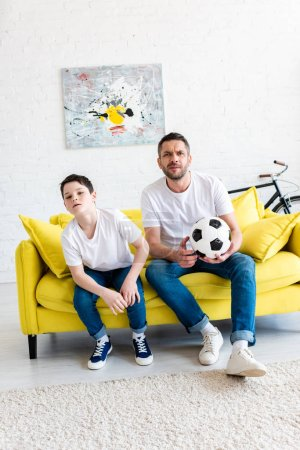 Photo for Father and son watching sports match on couch with soccer ball at home - Royalty Free Image