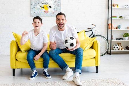 Foto de Padre e hijo animando mientras ve el partido de deportes en el sofá con la pelota de fútbol en casa - Imagen libre de derechos