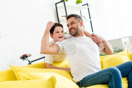 Photo for Son hugging happy father sitting on couch at home - Royalty Free Image