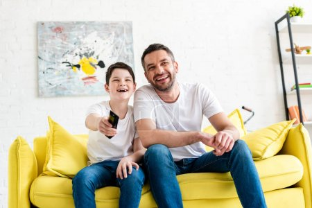 Photo pour Happy father and son sitting on couch and watching tv at home - image libre de droit