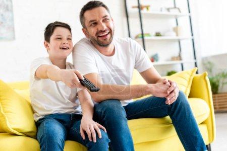 Photo pour Foyer sélectif du père et du fils heureux s'asseyant sur le divan et regardant la tv à la maison - image libre de droit