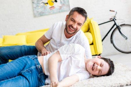Photo pour Père et fils heureux se trouvant sur le tapis et riant à la maison - image libre de droit