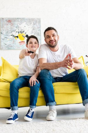 Photo for Father and son sitting on couch and watching tv at home - Royalty Free Image