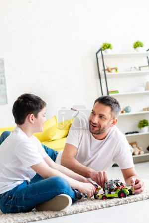 Foto de Padre e hijo sentados en la alfombra y jugando con el coche de juguete en casa - Imagen libre de derechos