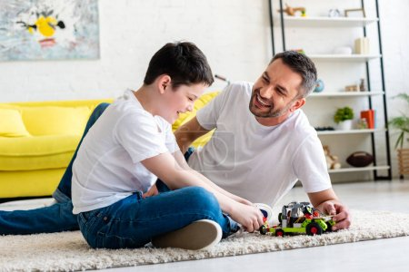 Photo for Happy father and son sitting on carpet and playing with toy car at home - Royalty Free Image