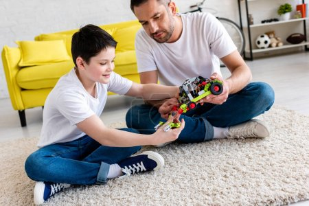 Photo for Father and son sitting on carpet and playing with toy car at home - Royalty Free Image