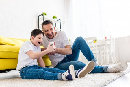 Photo for Excited father and son sitting on carpet and using smartphone in Living Room - Royalty Free Image