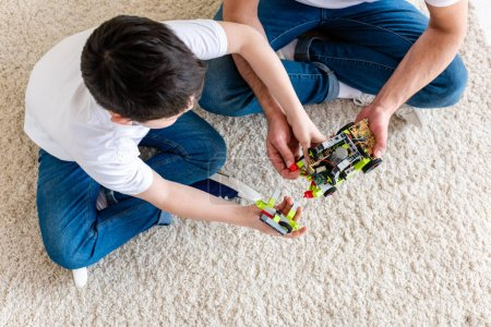 Photo for Top view of father and son sitting on carpet and playing with toy car at home - Royalty Free Image