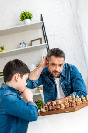 Foto de Guapo padre e hijo jugando ajedrez mientras se sienta en la mesa en casa - Imagen libre de derechos
