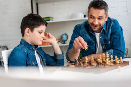 Photo for Selective focus of father and son in denim playing chess while sitting at table at home - Royalty Free Image