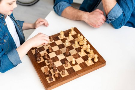 Photo for Cropped view of father and son in denim sitting at table and playing chess at home - Royalty Free Image